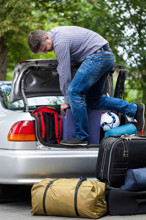 Man using his strength to packing luggage into car trunk