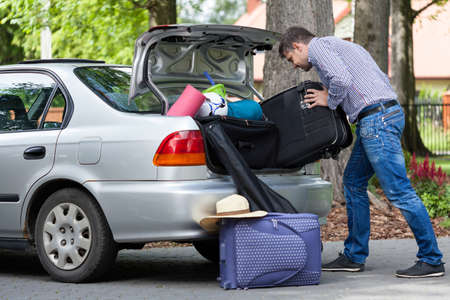 Horizontal view of a man trying to putting a travel bags into a car