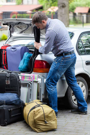 Vertical view of a man packing car for vacation