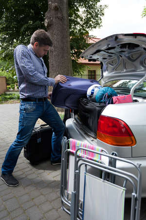Man pushing luggage into trunk of his car, vertical