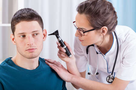 Young laryngologist examining patient by professional otoscope