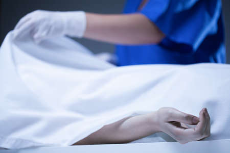 Worker of morgue covering corpse by sheet
