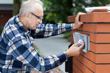 Older man repairing intercom at the gate