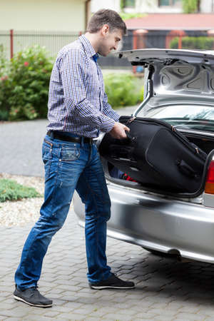 Man putting luggage into car trunk, vertical
