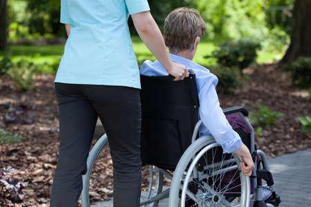 Close-up of a nurse pushing elderly woman on wheelchair