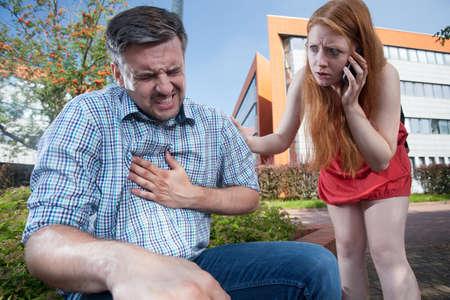 Man having heart attack and girl sending for ambulance