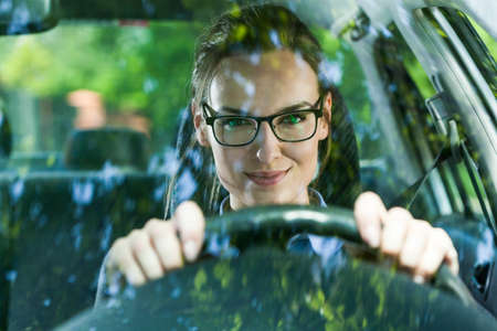 Young attractive woman in glasses driving a car