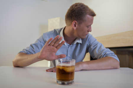 The young man refuses to drink a glass of whiskey