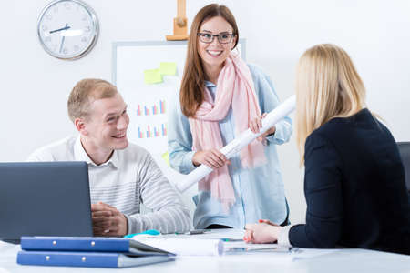 Happy young people working in modern workplace