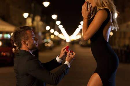 A man in a suit proposing to his beautiful woman at night