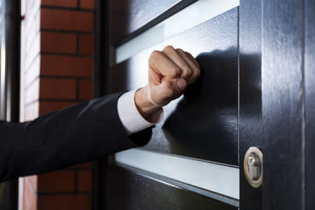 Close-up of hand knocking on the door