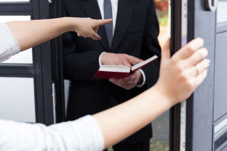 Woman ordering Jehovah's witness to go out