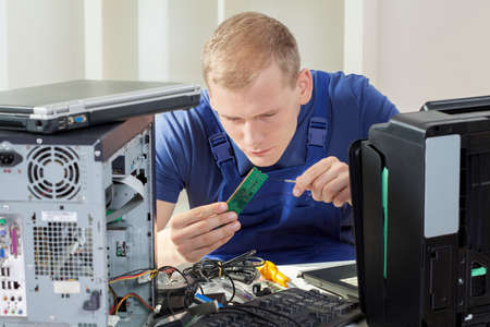 Young blonde IT specialist installing ram memory