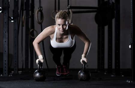 Young strong girl doing push-ups na kettlebells