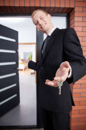 Smiling estate agent holding keys to beauty home