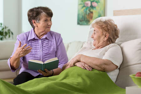 Elderly woman spending time with her sick friend in hospital