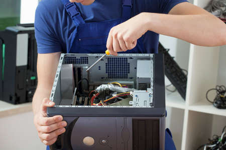 Close-up of man's hands who is trying to repair computer