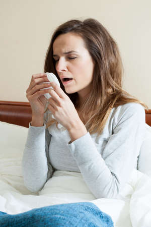 Young woman sitting upright in bed sneezing