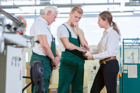 Photo pour Angry manager controlling employees in manufacturing plant - image libre de droit