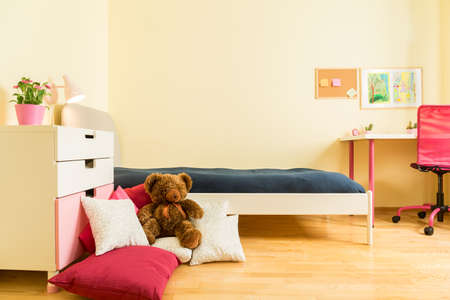 Cute children mascot on colorful pillows in bedroom