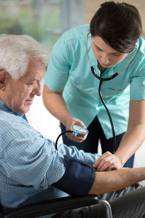 Young attractive nurse checking the elderly man's hypertension