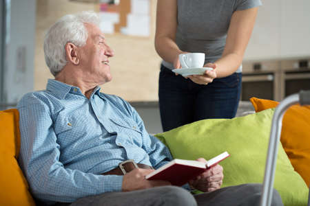 Photo pour Elderly happy man reading the book and his tea time - image libre de droit