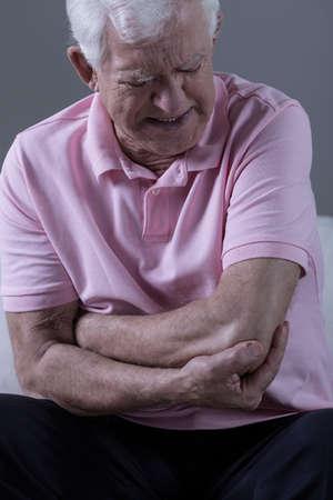 Senior man having painful elbow after injury
