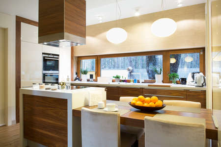 Modern bright wooden kitchen with island and big table