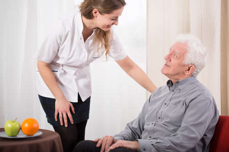 Image of young nurse caring about elder man