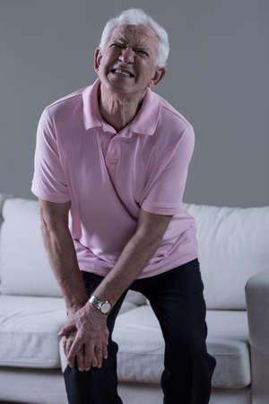 Senior man in terrible pain with injured knee