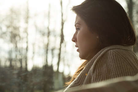 Close-up of young depressed crying woman sitting alone