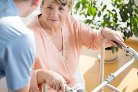 Horizontal view of nurse assisting disabled pensioner