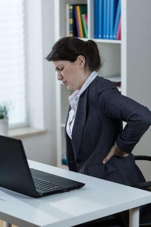 Office worker having backache caused by sedentary work