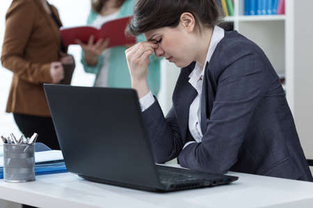 Female clerk having sinus pain at work
