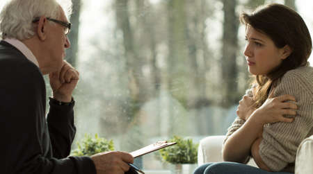 Young woman during visit at psychotherapist's office