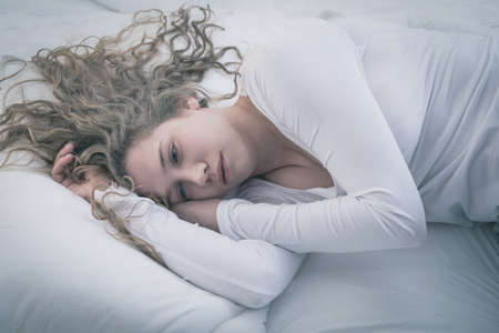 Young attractive woman in deep depression lying alone