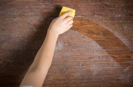 Using yellow sponge for cleaning dusty wood