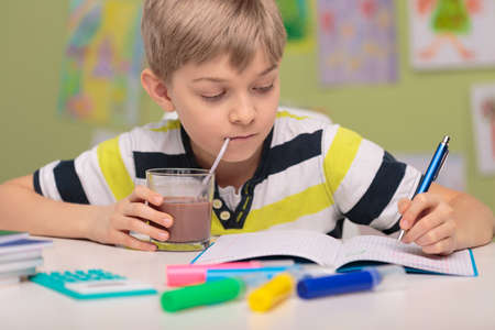 School child doing homework and drinking cacao