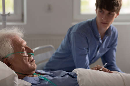 Older ill man with nasal cannula sleeping in hospital bed