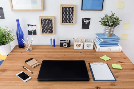 Laptop and mobile phone on wooden office table