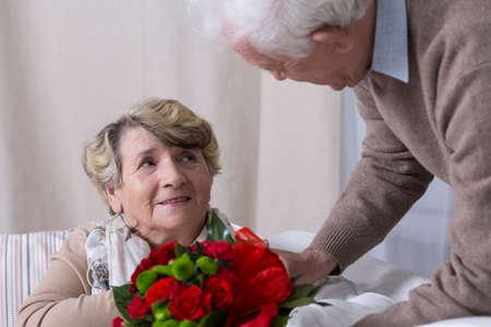 Senior husband giving his wife anniversary gift