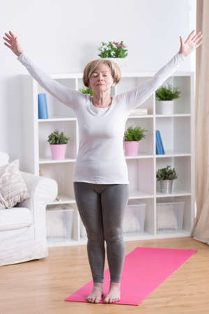 Foto per Senior woman taking deep breath during morning yoga - Immagine Royalty Free