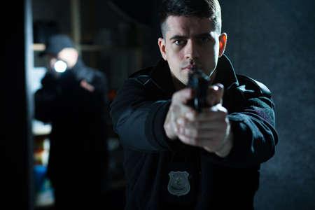 Image of a confident handsome policeman holding a handgun