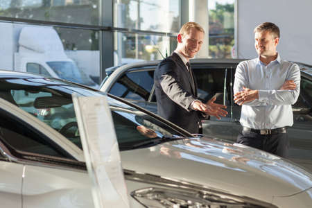 Young man working as salesman in car dealership