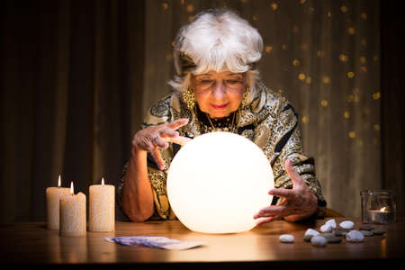 Photo of woman foretelling future from crystal ball