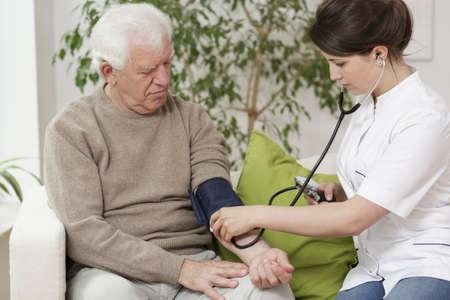 Doctor measuring blood pressure of elder man