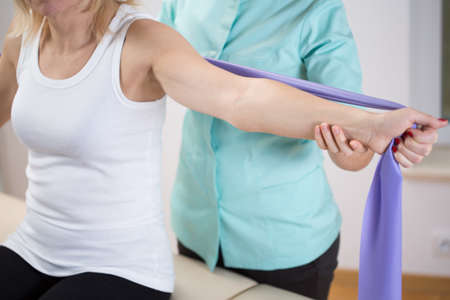 Woman at physiotherapist office exercising with band
