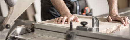 Carpenter is cutting a piece of wood