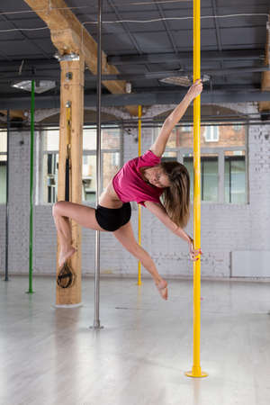 Image of young pretty dancer spinning around the pole