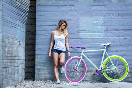 Photo of sporty girl and her trendy colorful bike